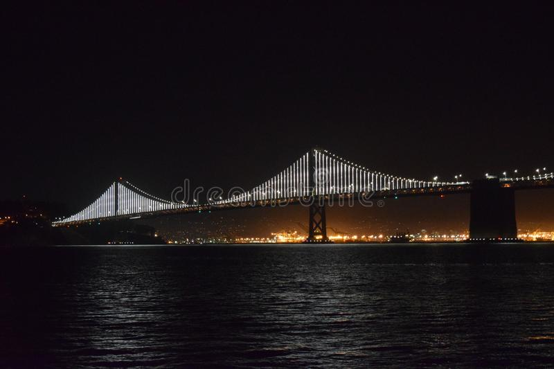Wide shot of the lighted Bay Bridge on the body of water in San Francisco, California during night. A wide shot of the lighted Bay Bridge on the body of water in stock photos