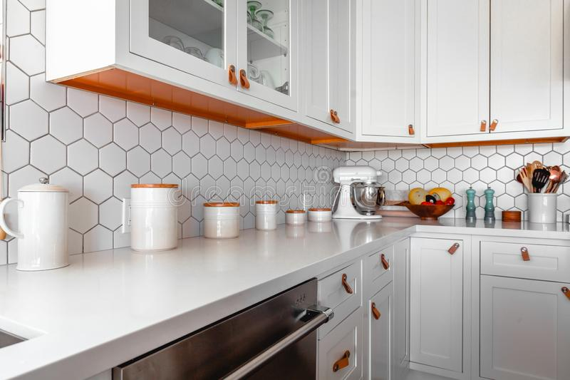 Wide shot of a modern kitchen interior with various sized white ceramic jars and other kitchenware stock image