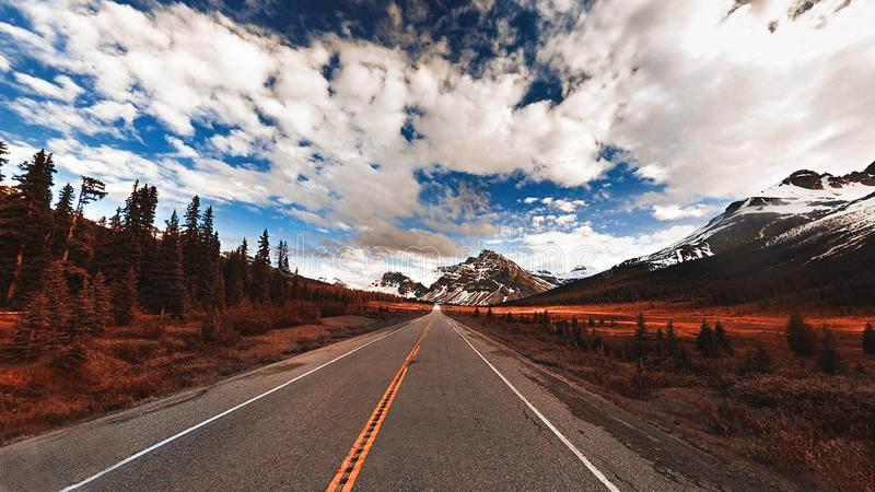 Wide shot of a narrow road with amazing clouds in the sky and beautiful snowy hills on the side royalty free stock photos
