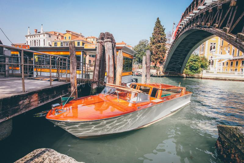 Wide shot of an orange waterway boat on a river under a bridge near buildings in Venice, Italy stock photos