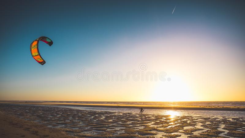 Wide shot of a of a person kitesurfing by the beach captured at sunset in Oostkapelle, Netherlands stock photos