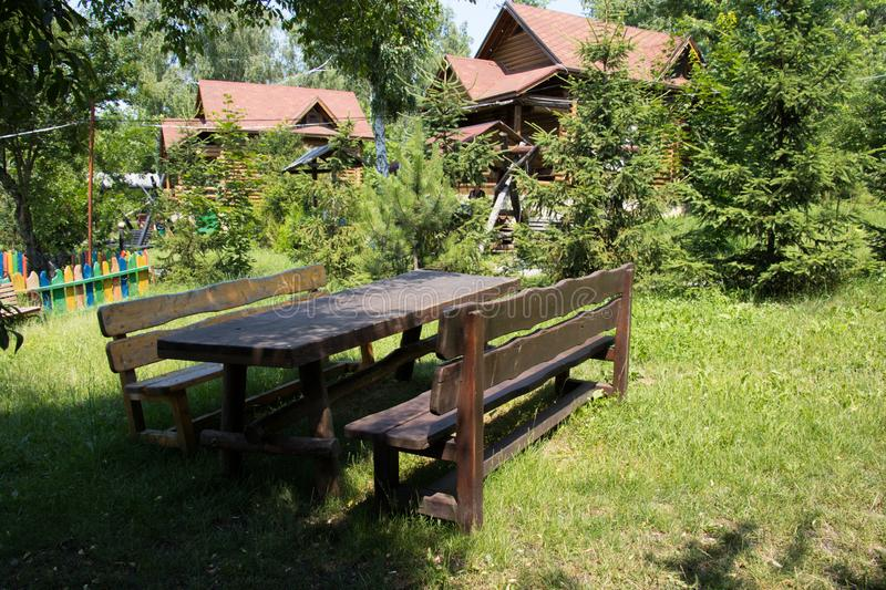 Wide shot of a picnic table in the park in front of cabin with red rooftops. A wide shot of a picnic table in the park in front of cabin with red rooftops royalty free stock photos