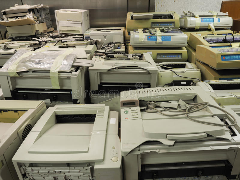 Wide shot of pile or stack of old printers that are out of date. Outdated old printers are waiting for an auction or sell away as office trash royalty free stock photo