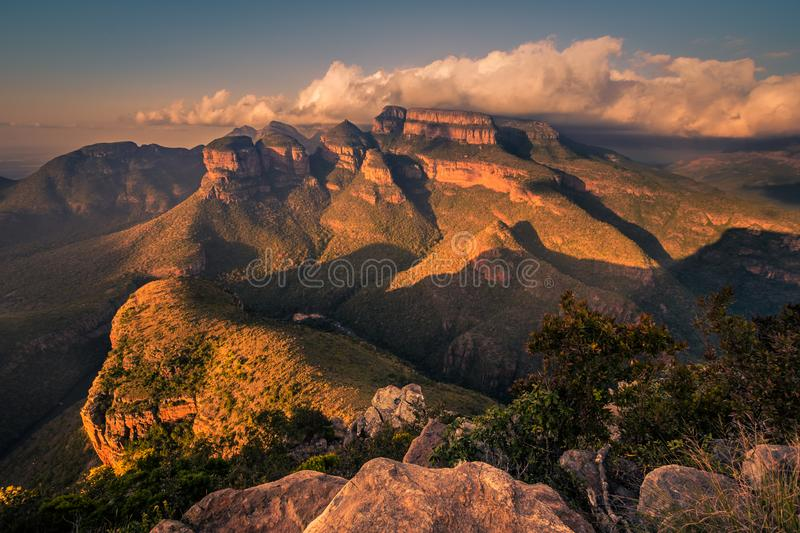 A wide shot of the Three Rondavels and surrounding landscape lit stock photography