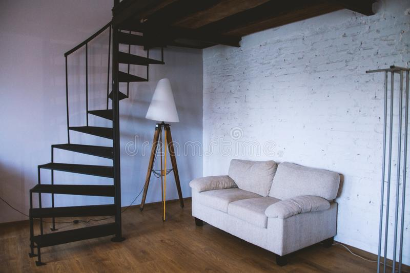 Wide shot of a white sofa near a lamp stand in a room with black spiral stairs stock photos