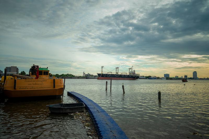 Wide shot of a yellow boat and cargo ship on the body of water under a cloudy sky royalty free stock photography