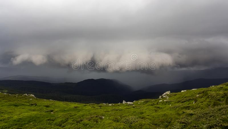 Wide summer mountain panorama before thunderstorm. Dark rain clouds low over green grassy rocky valley and distant mountain range stock photo
