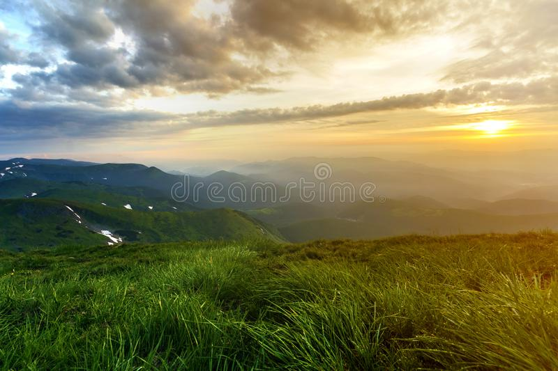 Wide summer mountain view at sunrise. Glowing orange sun raising in blue cloudy sky over green grassy hill soft grass and distant. Mountain range covered with stock images