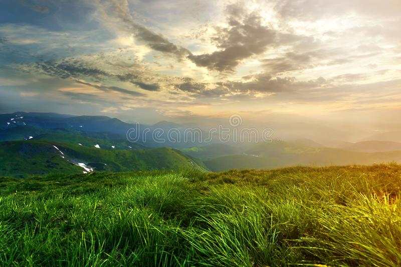 Wide summer mountain view at sunrise. Glowing orange sun raising in blue cloudy sky over green grassy hill soft grass and distant. Mountain range covered with stock photo