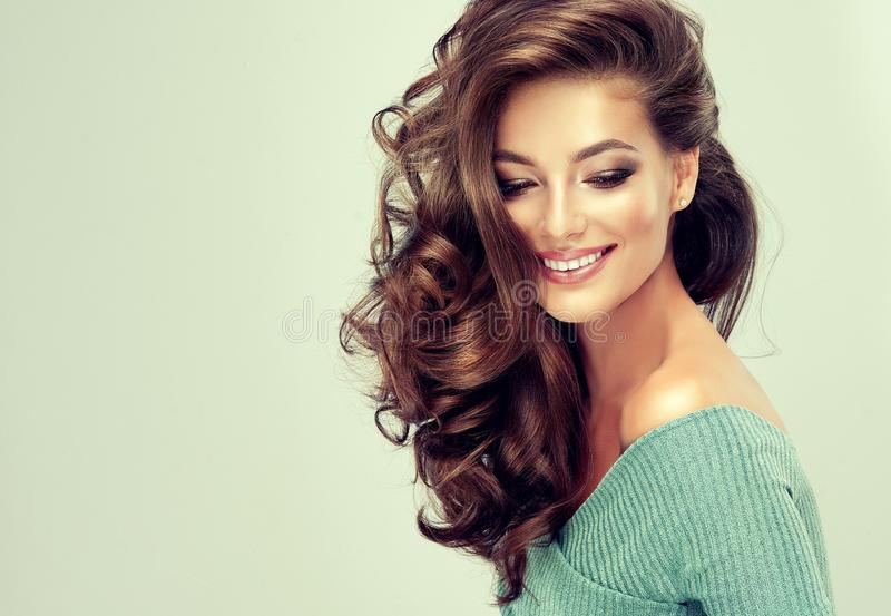 Wide, toothy smile on the face of young, brown haired beautiful model with long, curly, well groomed hair. Excellent hair wav royalty free stock photos