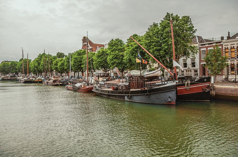 Wide tree-lined canal with brick buildings in a street next to it and moored boats in a cloudy day at Dordrecht. Important and historic port city bordered by royalty free stock photos