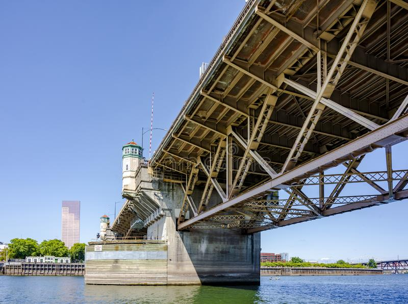 Burnside Bridge with buscle mechanism on Willamette River. Wide truss Burnside drawbridge with towers on concrete supports with hoisting mechanisms for raising royalty free stock images