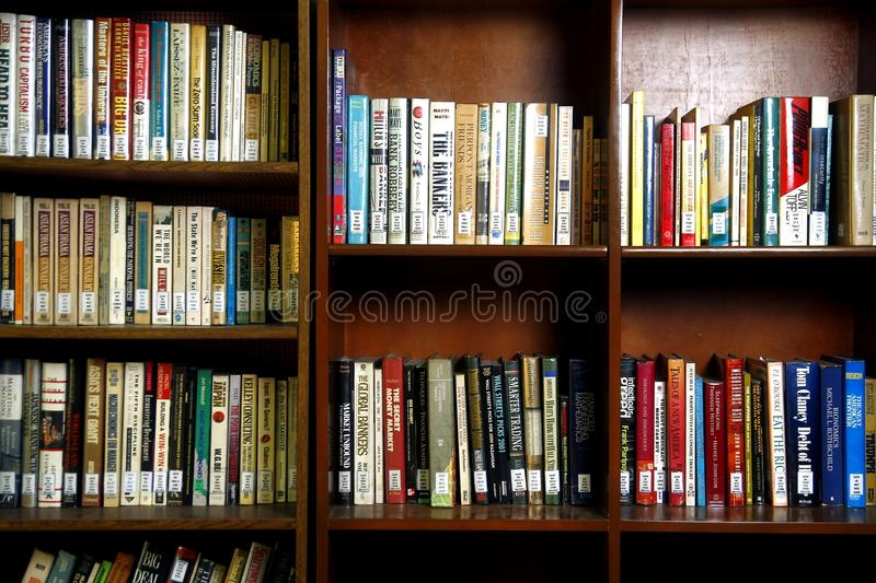 A wide variety of books on wooden shelves inside a library. stock photo