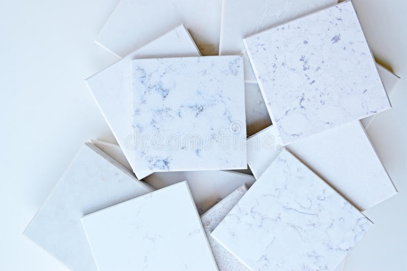 Wide variety of stone samples mainly marble like grains and veins stacked up together with empty space around. Samples of different stones in square shape royalty free stock photography