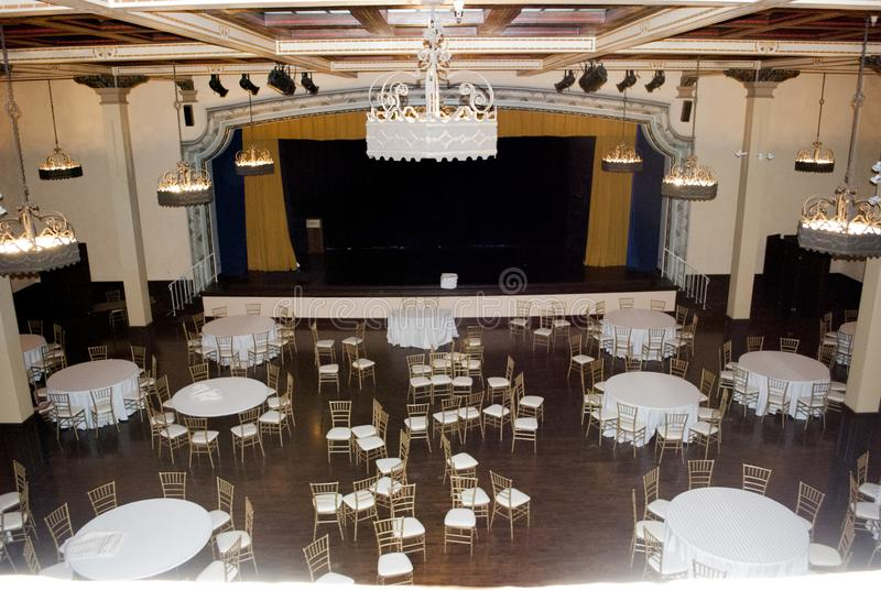 Wide view on banquet ball room in vintage style with lot of tables, chairs and theater scene royalty free stock image