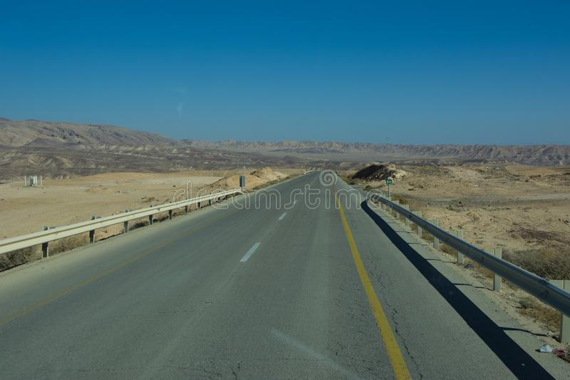 Wide view of desert road through the Isreal southwest. View of desert road through the Isreal southwest royalty free stock images