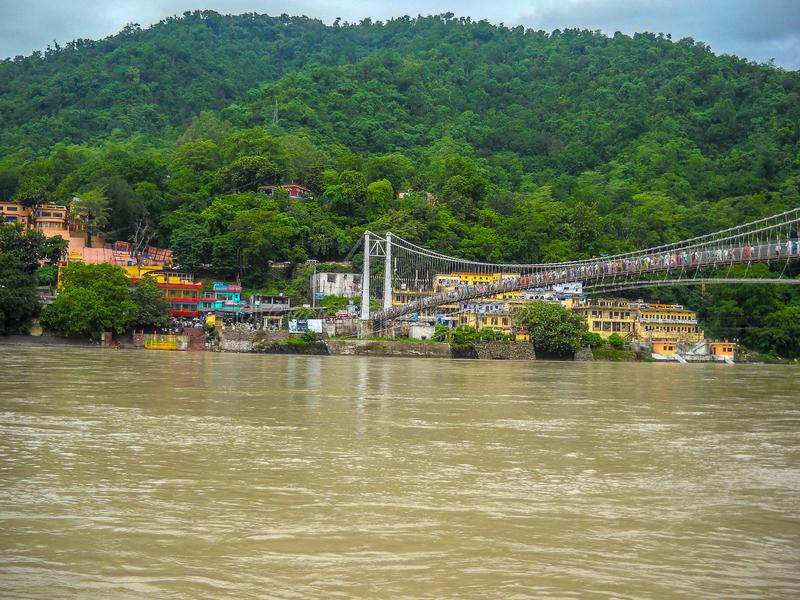 Wide view of Ganga river in Rishikesh India. Cable rope bridge over the Ganga river stock photography