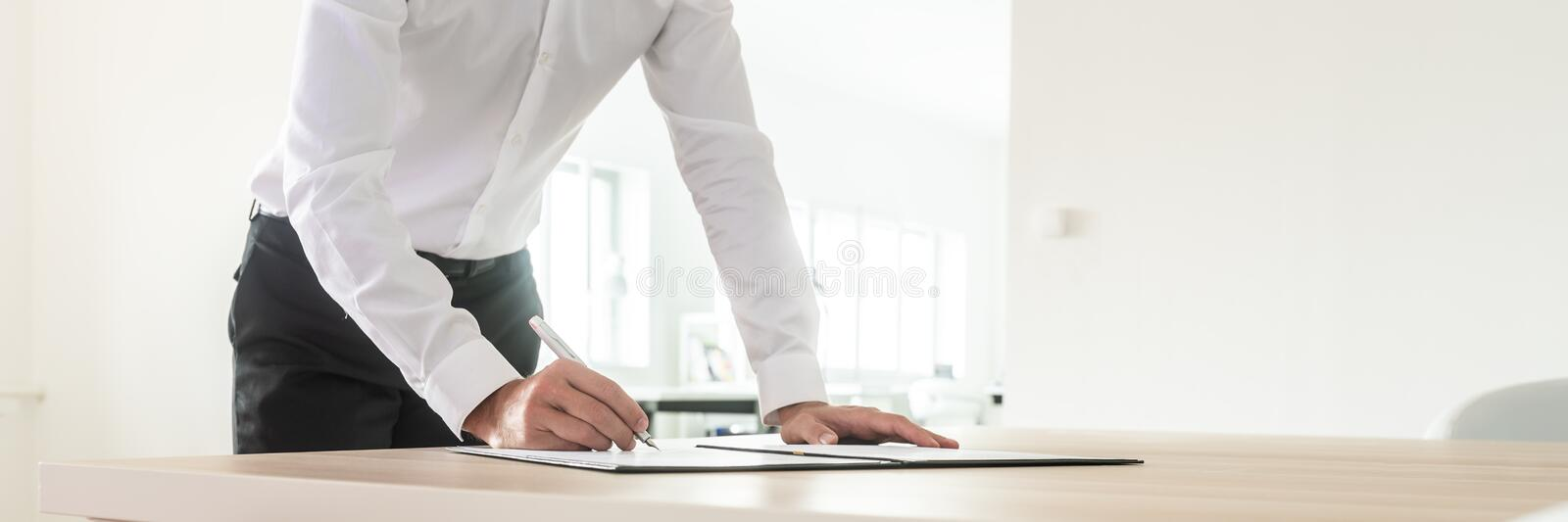 Wide view image of businessman signing a document. Wide view image of businessman standing at his office desk leaning forward as he signs an investment document royalty free stock photos