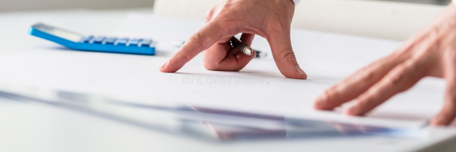 Wide view image of an engineer working on a project. With calculator and ruler on his paper royalty free stock photography