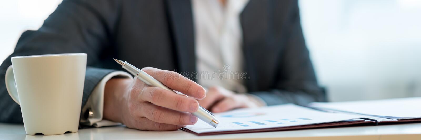 Wide view image of an entrepreneur reviewing business report stock photography