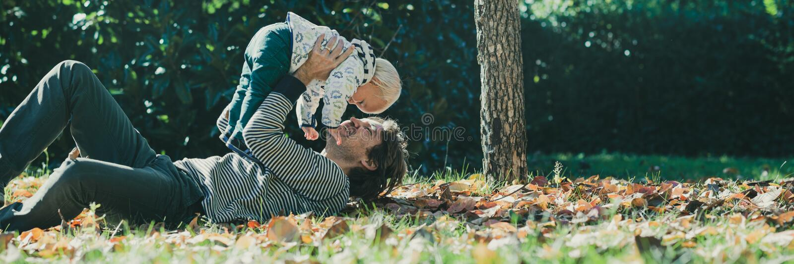 Happy young father playing with his son stock photo