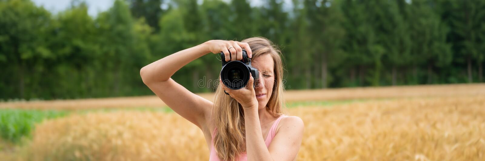 Wide view image of a young female photographer taking a photo stock image