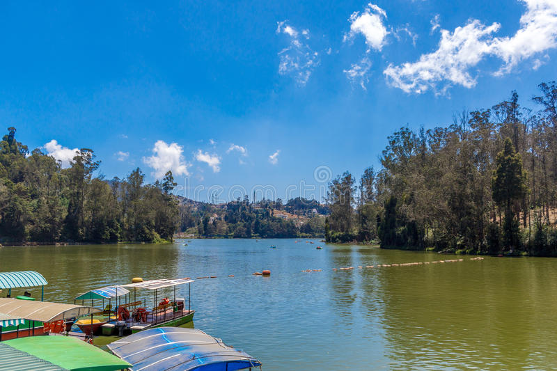 Wide view of lake with boats, beautiful tress in the background, Ooty, India, 19 Aug 2016. Wide view of lake with boats, beautiful tress in the background stock images