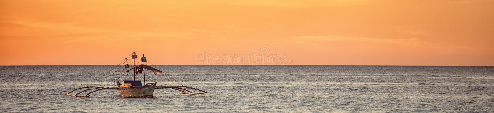 A wide view of the sea and a boat at a sunset royalty free stock image
