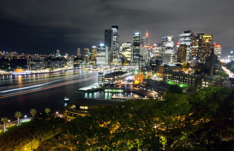 Wide view of Sydney CBD cityscape at night with light trails from ferry traffic in Circular Quay royalty free stock photography