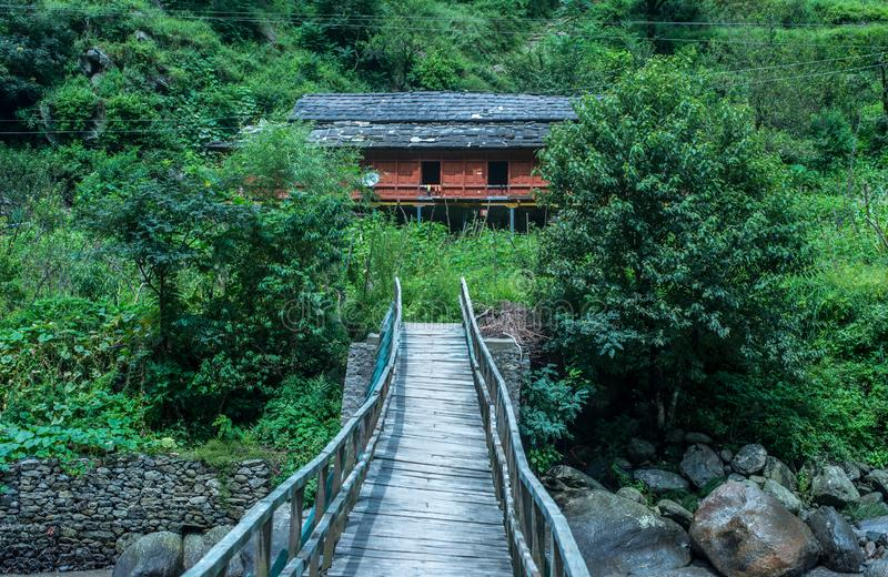 Wide view of a wooden bridge crossing a river bend leading to a house in himalaya, India. Wide view of a wooden bridge crossing a river bend leading to a house stock photos