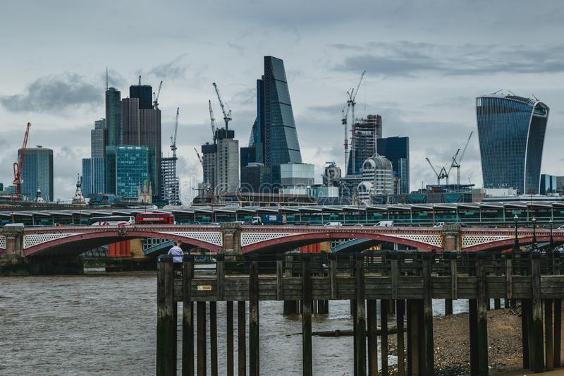 Wide Vista of Iconic London Skyscrapers. A wide view of some of London`s beautiful modern skyscrapers surrounded by the ever-present construction cranes royalty free stock images