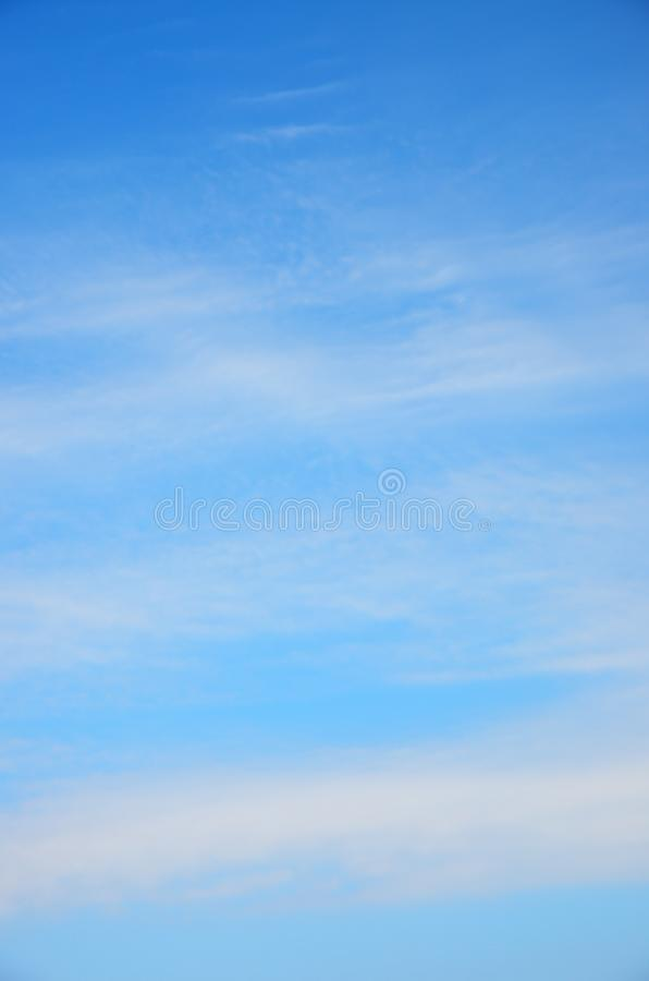 White fuzzy stripes clouds in blue sky royalty free stock photo