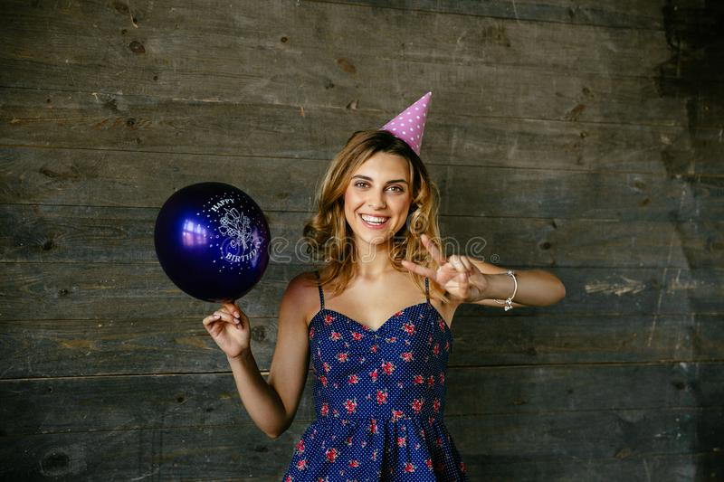 Widely smiling woman in birthday hat celebrating holiday. Cheerful excited girl having fun while celebrating birthday, showing peace sign, holds a balloon royalty free stock images