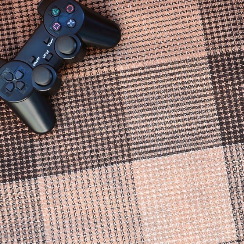 Wideo gry kontroler od gemowej konsoli jest na w kratkę kanapie Urządzenie bezprzewodowe dla kontrolować podczas wideo gry zdjęcie royalty free