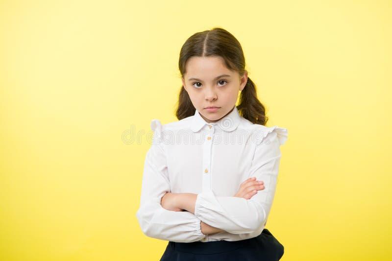 Widerspruch und Hartnäckigkeit Beleidigter gelber Hintergrund der Mädchenschuluniform ernstes Gesicht Kinderunglückliche Blicke a stockfotografie