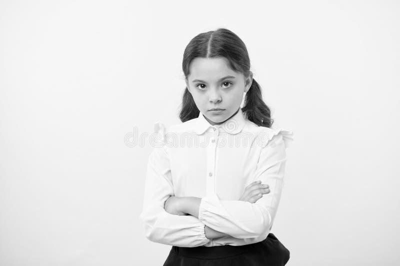 Widerspruch und Hartnäckigkeit Beleidigter gelber Hintergrund der Mädchenschuluniform ernstes Gesicht Kinderunglückliche Blicke a lizenzfreie stockfotografie