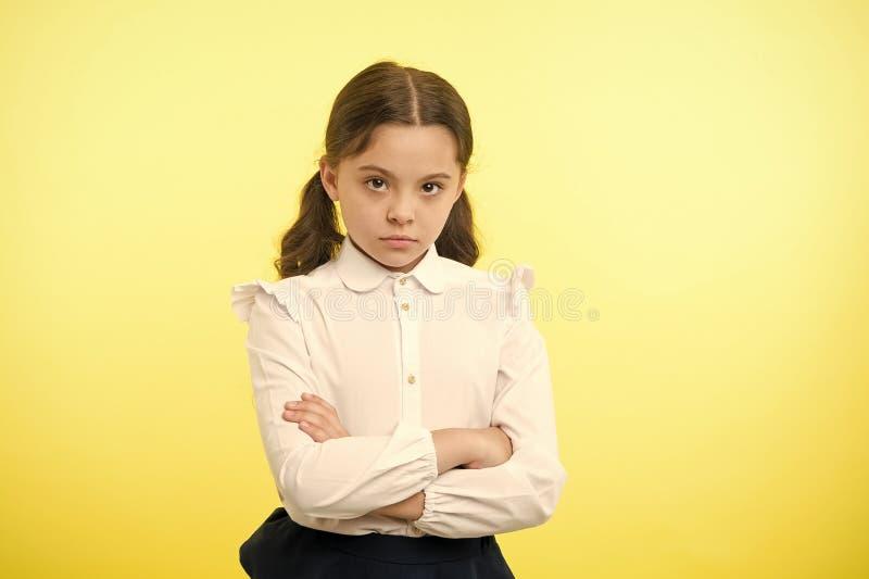 Widerspruch und Hartn?ckigkeit Beleidigter gelber Hintergrund der M?dchenschuluniform ernstes Gesicht Kinderungl?ckliche Blicke a stockfoto