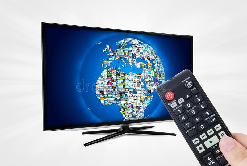 Widescreen high definition TV screen with sphere video gallery. Remote control in hand stock photos