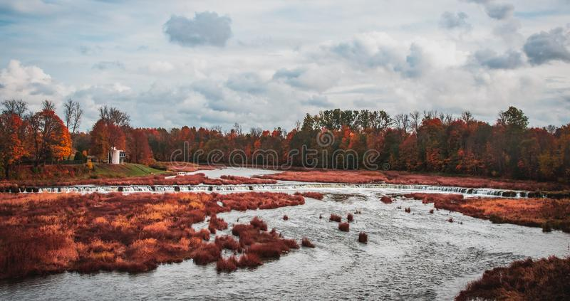 The widest waterfall in Europe in the town of Kuldiga, Latvia. Autumn, colora, colors, season, motion, plants, trees, forest, woods, sky, clouds, turism royalty free stock photo