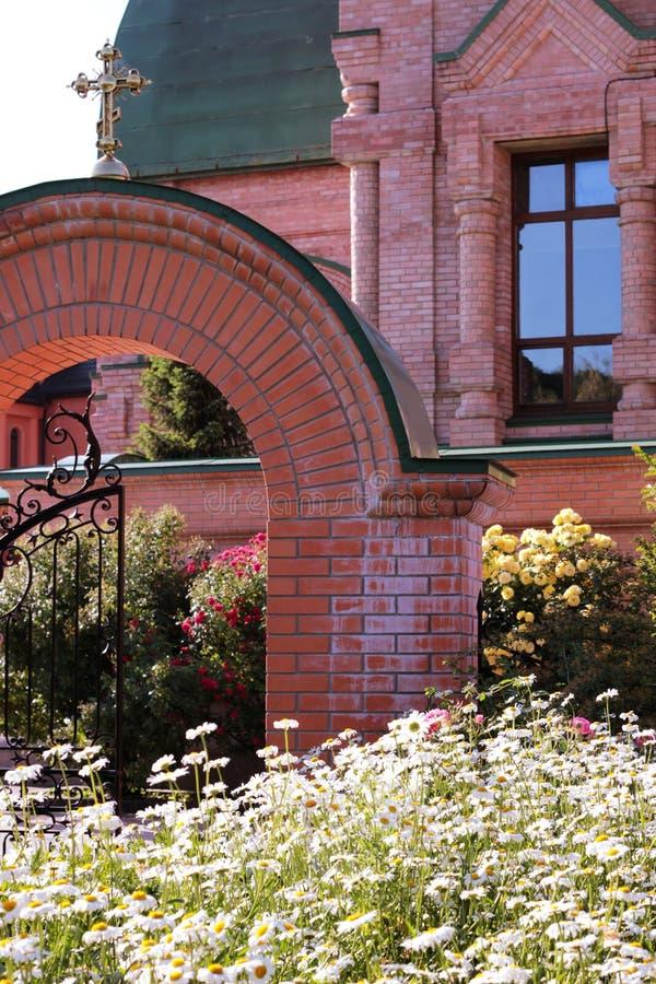 Widok łuk i fałszujący ogrodzenie z powodów ukrzyżowanego kościół piękny, cegła, Białe stokrotki i róże r fotografia royalty free