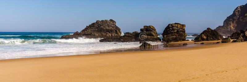 Widok Adraga piaskowata plaża z kamieniami blisko Sintra, Portugalia skalisty wybrzeże zdjęcia stock
