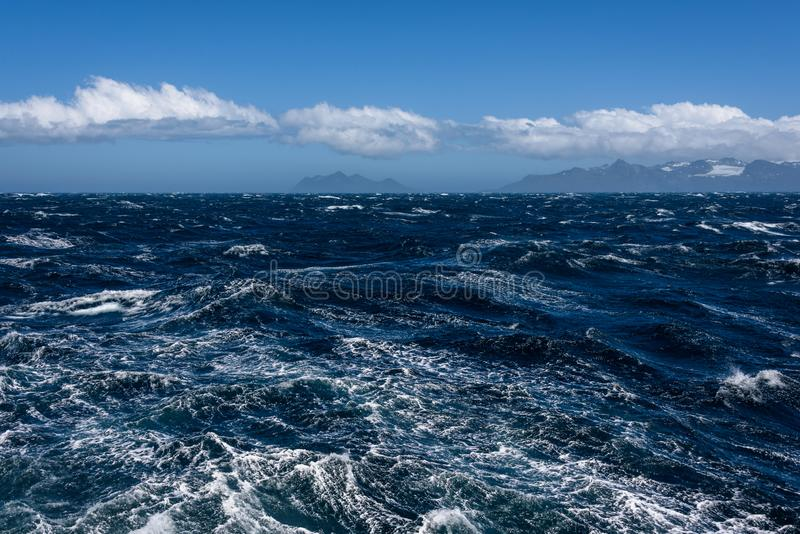 Widok Atlantycki ocean i odległe góry, choppy woda, spokojny niebieskie niebo z białymi chmurami obraz royalty free