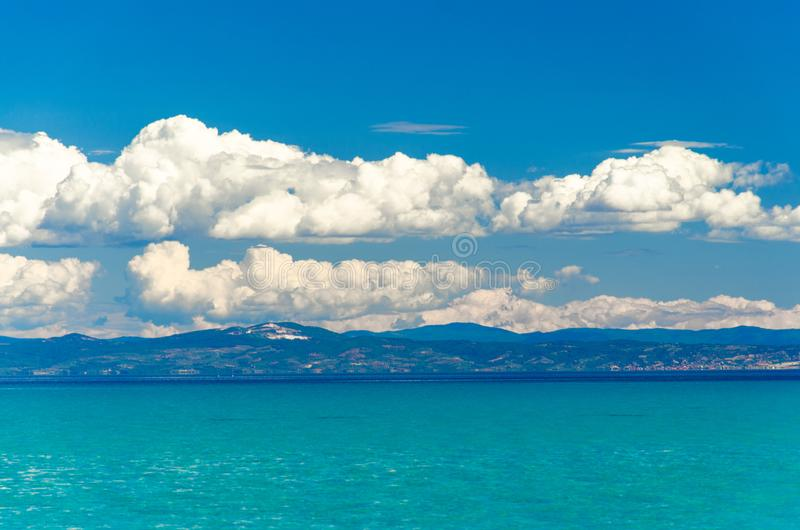 Widok błękitna raj woda zatoka, niebieskie niebo i biel Toroneos kolpos, chmurnieje nad Sithonia półwysepem widzieć od Halkidiki fotografia stock