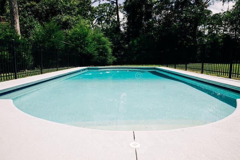 Widok basenu podwórkowego poza domem z dużą ilością Tam jest czarny metalowy płot obrazy stock