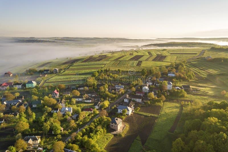 Widok biała mgła na wioska domu dachach wśród zielonych drzew pod jaskrawym niebieskim niebem z góry Wiosny mglista krajobrazowa  obraz stock