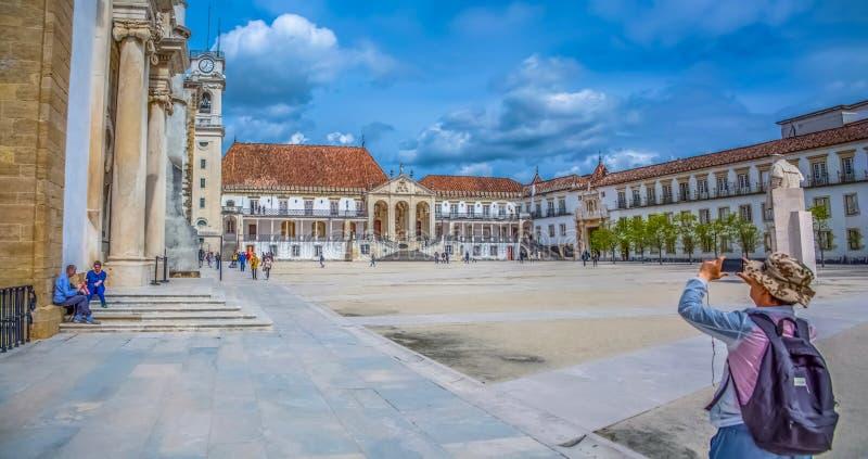 Widok bierze fotografie z telefonem komórkowym turystyczny mężczyzna, w placu uniwersytet Coimbra, Portugalia zdjęcie royalty free