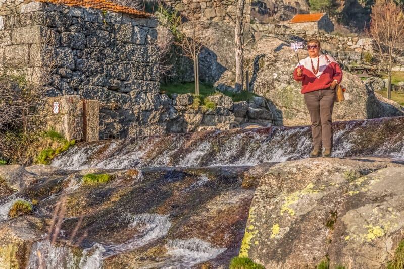 Widok bierze obrazki z telefonem komórkowym na kiju stara kobieta, blisko rzeki z wielkimi granitic skałami zdjęcie royalty free