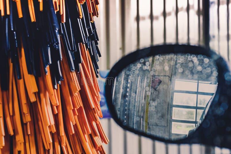 Widok boczny lustro pomarańcze i samochód szczotkuje na automatycznym samochodowym obmyciu fotografia stock