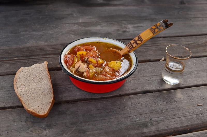 Widok drewniany stół z czerwonym metalu talerzem z pomidorową polewką w domu z ajerówką w szklanej zlewce, czarnym chlebie i Rosj zdjęcia stock