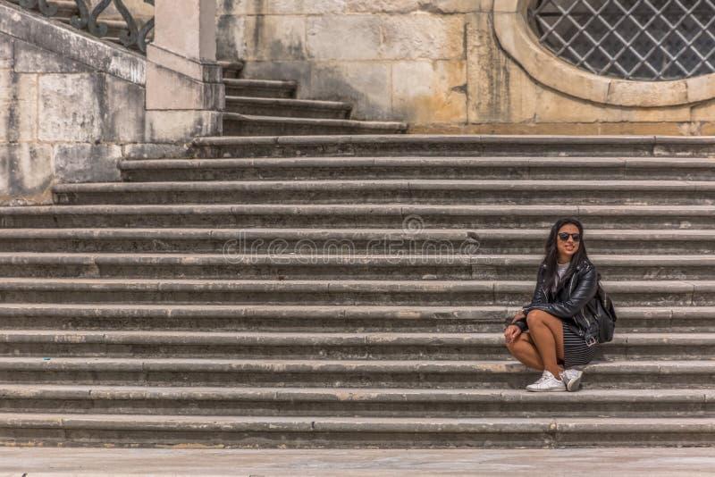 Widok dziewczyny obsiadanie na schodkach uniwersytet prawo w Coimbra, spojrzenia przy przyjaciółmi brać fotografię w Coimbra, Por zdjęcie royalty free